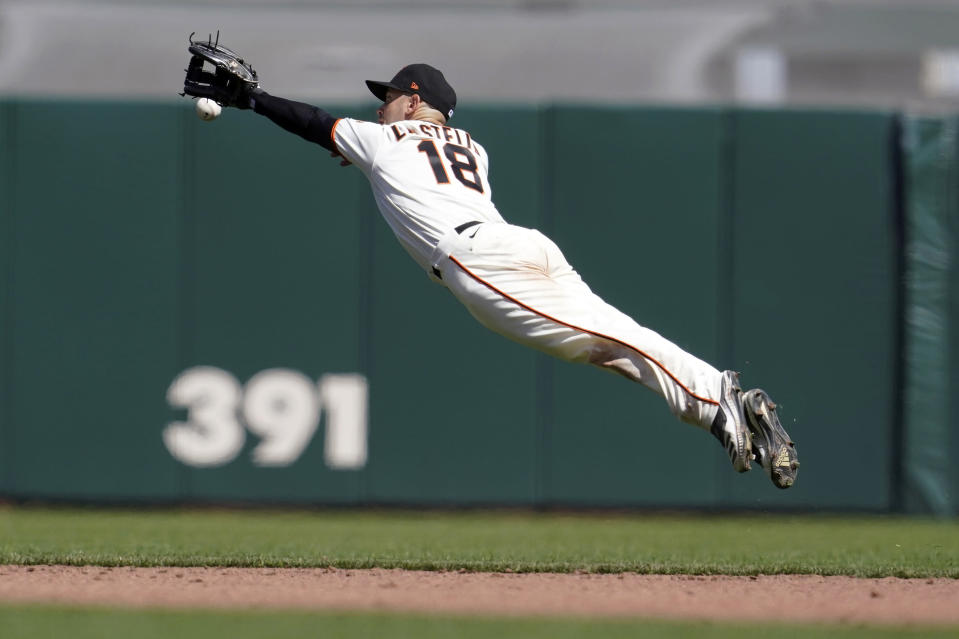 San Francisco Giants second baseman Tommy La Stella (18) dives but cannot reach a single by Colorado Rockies' Chi Chi Gonzalez during the fifth inning of a baseball game in San Francisco, Saturday, April 10, 2021. (AP Photo/Jeff Chiu)