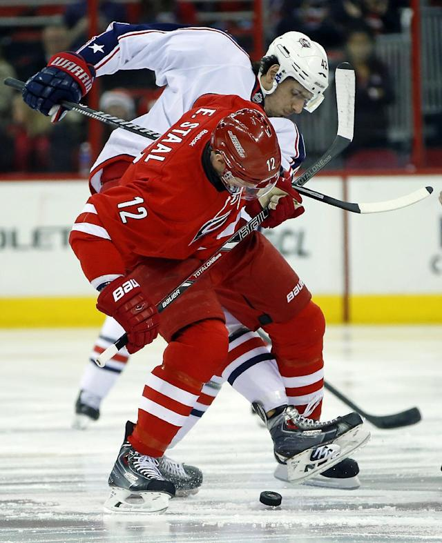 Carolina Hurricanes' Eric Staal (12) tangles with Columbus Blue Jackets' Artem Anisimov (42), of Russia, during the first period of an NHL hockey game in Raleigh, N.C., Monday, Dec. 23, 2013. (AP Photo/Karl B DeBlaker)