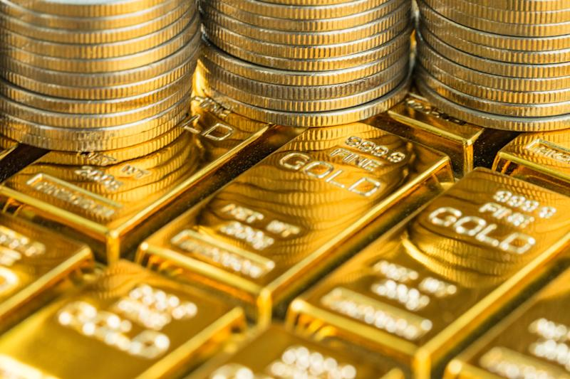 Stacks of gold coins sit on rows of gold bars.
