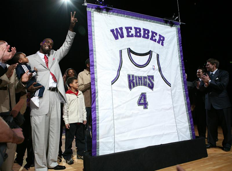 Former Sacramento Kings forward Chris Webber, left, waves to fans as his jersey is retired during a ceremony at halftime of an NBA basketball game against the Utah Jazz in Sacramento, Calif., Friday, Feb. 6, 2009. Webber is holding his nephew, 2-year-old Jordon Webber. (AP Photo/Steve Yeater)