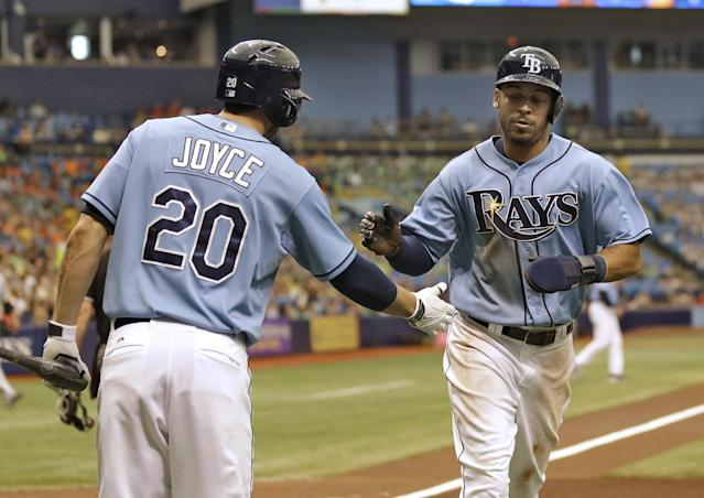 Tampa Bay Rays' Desmond Jennings, right, shakes hands with on-deck batter Matt Joyce after scoring on a triple by teammate Ben Zobrist off Pittsburgh Pirates starting pitcher Charlie Morton during the first inning of an interleague baseball game Wednesday, June 25, 2014, in St. Petersburg, Fla. (AP Photo/Chris O'Meara)