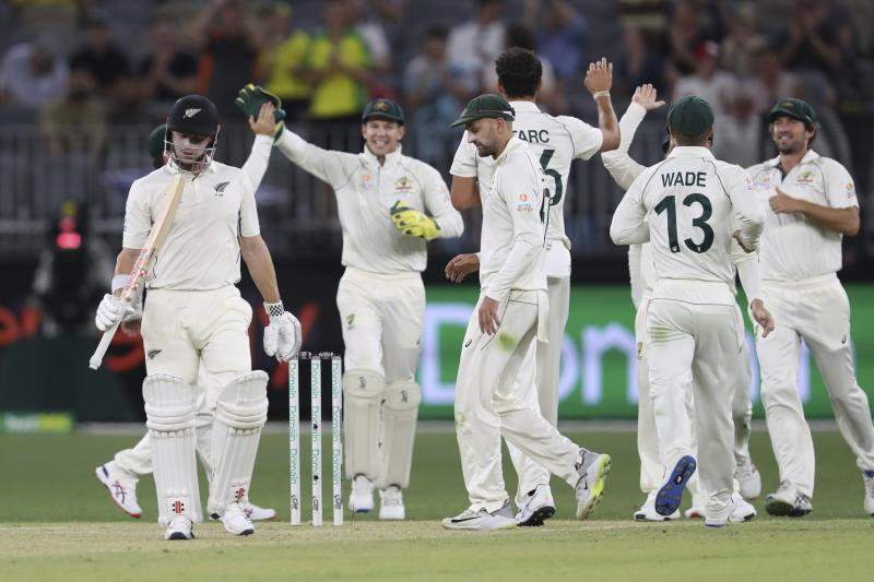 New Zealand's Henry Nicholls, second left, looks at his bat as he leaves the field after being dismissed during their cricket test match against Australia in Perth, Australia, Friday, Dec. 13, 2019. (AP Photo/Trevor Collens)