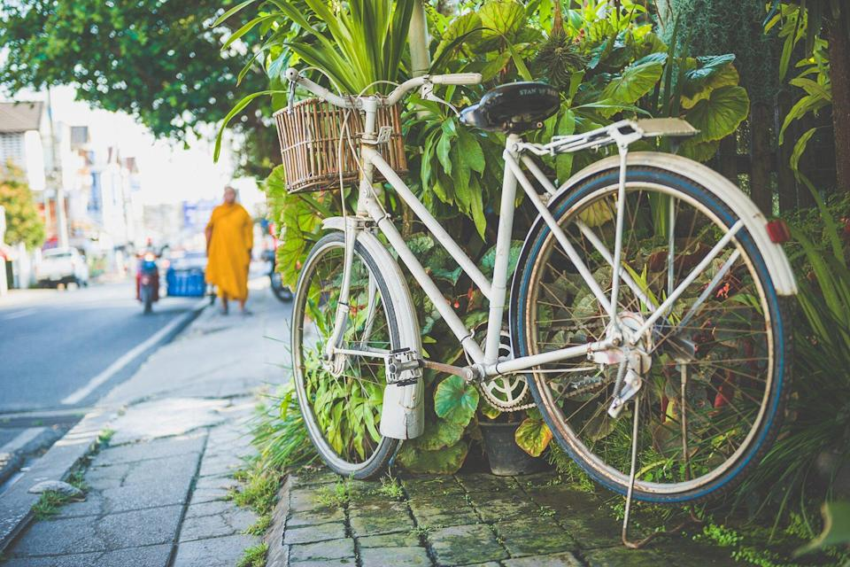An old white bicycle parked on the street in Chiang Mai in Thailand