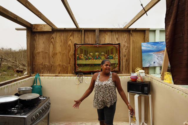 <p>Single mother Omayra Cruz, 44, returned from a food distribution with a box she would share with 4-year-old son Nene. But the two were still living without a roof, sleeping under the stars next to a pig pen, and a picture of the Last Supper. Their water tank had a few inches left. (Photo: Carolyn Cole/Los Angeles Times via Getty Images) </p>