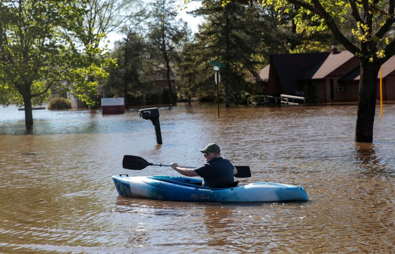 Resident Joe Ryan paddles a kayak to check on his home in a flooded neighborhood along the Tittabawassee River, after the two dam failures in Midland, Michigan