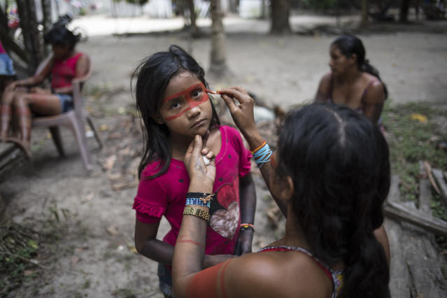 In this Sept. 4, 2019 photo, a child stands still as a woman paints a red mask around her eyes, in preparation for a gathering of tribes in the Alto Rio Guama Indigenous Reserve by the Tembe tribes in the village Tekohaw, Para state, Brazil. The indigenous reserve is officially protected, but it's constantly under siege by loggers who illegally try to extract prized hardwood. (AP Photo/Rodrigo Abd)