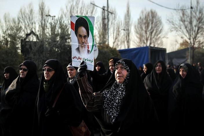 Iranian women carry a placard showing revolutonary leader Ayatollah Ruhollah Khomeini as they march in support of the regime he founded in Tehran on December 30, 2017 (AFP Photo/HAMED MALEKPOUR)