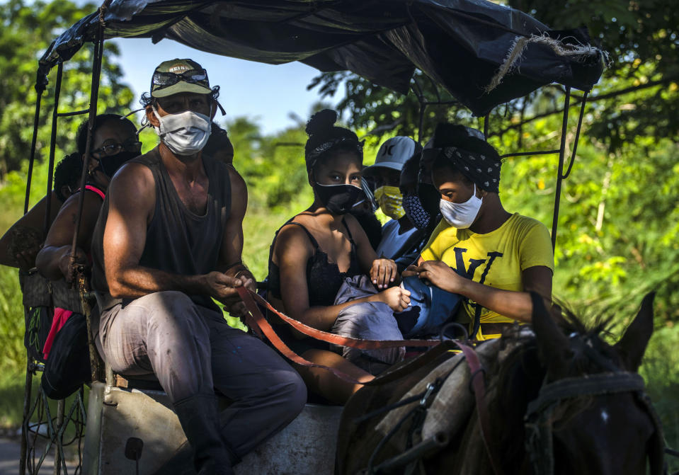 People wearing masks as a precaution against the spread of the new coronavirus travel to the beach in a horse cart in Havana, Cuba, Sunday, Oct. 11, 2020. (AP Photo/Ramon Espinosa)