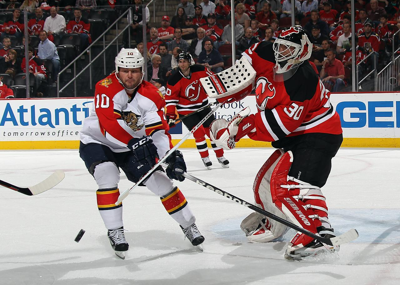 NEWARK, NJ - APRIL 19: Martin Brodeur #30 of the New Jersey Devils shoots the puck clear of former teammate John Madden #10 of the Florida Panthers  in Game Four of the Eastern Conference Quarterfinals during the 2012 NHL Stanley Cup Playoffs at Prudential Center on April 19, 2012 in Newark, New Jersey.  (Photo by Bruce Bennett/Getty Images)