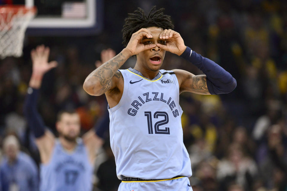 Memphis Grizzlies guard Ja Morant (12) reacts after an assist to center Jonas Valanciunas (17) in the second half of an NBA basketball game against the Los Angeles Lakers, Saturday, Feb. 29, 2020, in Memphis, Tenn. (AP Photo/Brandon Dill)