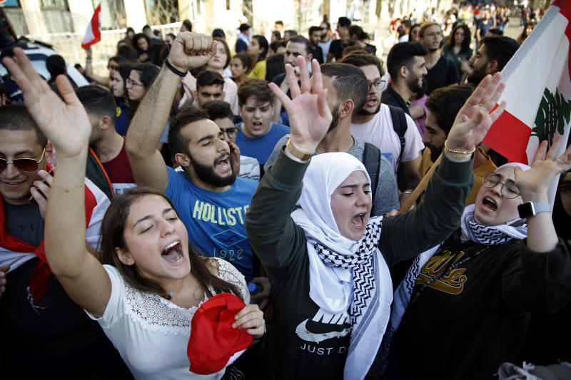 University students chant slogans against the Lebanese government, in Beirut, Tuesday, Nov. 12, 2019. Protesters in Lebanon resumed demonstrations on Tuesday blocking some roads and governmental institutions. (AP Photo/Bilal Hussein)