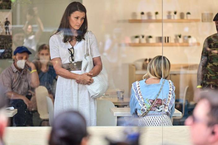 <p>Bridget Moynahan wears a belted white dress and carries an oversized tote bag during a moment with Parker. </p>