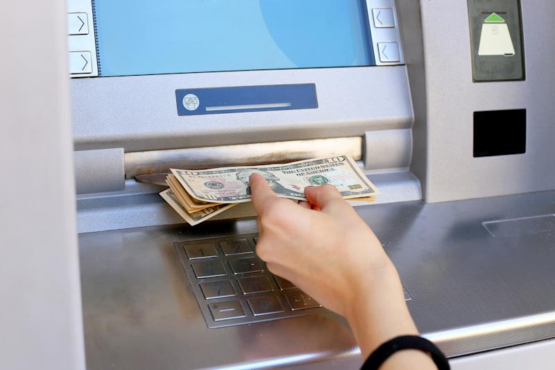 A hand pulling money out of an ATM