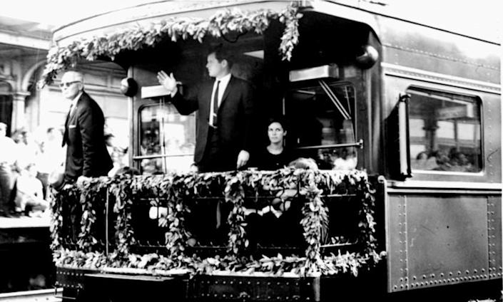 Sen. Edward M. Kennedy waves from the rear platform of the observation car