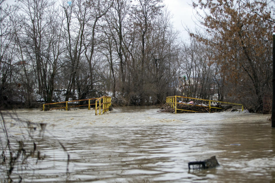 A bridge on the road that leads to the village of Preoc is flooded following heavy rain and snowfall, Kosovo on Monday, Jan. 11, 2021. Many roads have been blocked and bridges damaged, according to the authorities. There have been no casualties or lost livestock so far. (AP Photo/Visar Kryeziu)