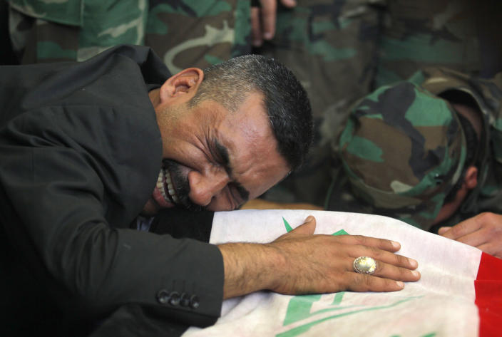 FILE - In this file photo taken Saturday, April 26, 2014, a man mourns over the flag-draped coffin of his son during a funeral procession for five militia members of a Shiite group, Asaib Ahl al-Haq, or League of the Righteous, in the Shiite holy city of Najaf, 100 miles (160 kilometers) south of Baghdad, Iraq. As parliamentary elections are held Wednesday, April 30, more than two years after the withdrawal of U.S. troops, Baghdad is once again a city gripped by fear and scarred by violence. (AP Photo/Jaber al-Helo, File)