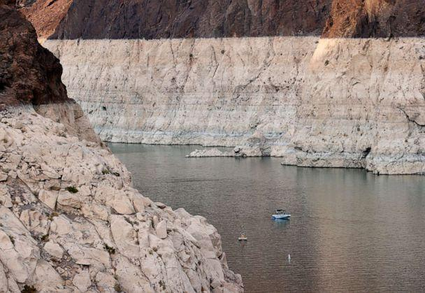PHOTO: A boat cruises past mineral-stained rocks on the upstream side of the Hoover Dam, June 15, 2021, in the Lake Mead National Recreation Area, Nevada. (Ethan Miller/Getty Images)