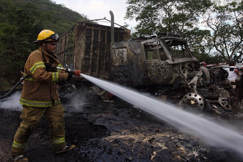 Firefighters work on a burned truck at Gomez Morin Avenue in the Guadalajara - Autlan highway in Jalisco state, Mexico, on May 1, 2015, amid escalation of violence by the Jalisco New Generation Drug Cartel (AFP Photo/Hector Guerrero)