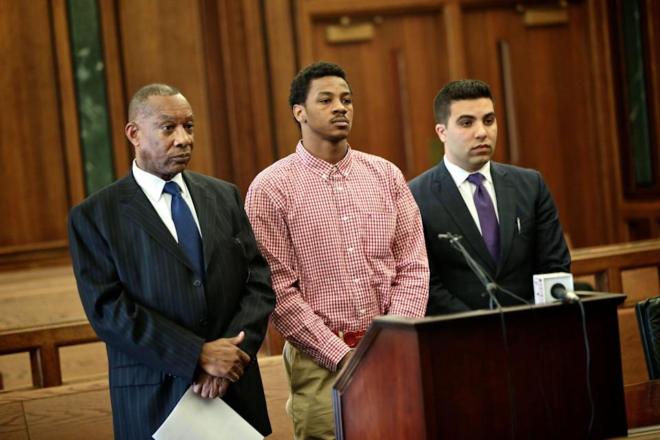 Former Michigan State basketball star Keith Appling, center, stands alongside his attorneys, Cyril C. Hall, left, and Amir I. Makled, during an arraignment May 4, 2016, in Dearborn.