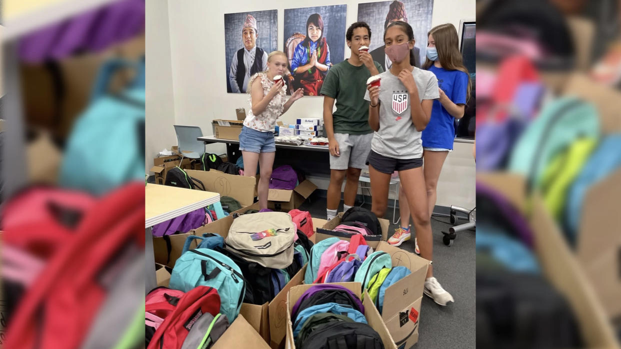 Lily, left, and friends at New American Pathways with some of the backpacks for Afghanistan refugee children going back to school. (Photo: New American Pathways)