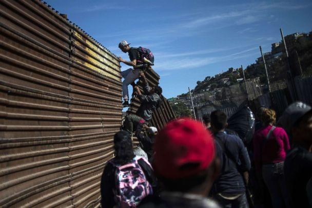 PHOTO: A group of Central American migrants climb the border fence between Mexico and the United States, near El Chaparral border crossing, in Tijuana, Mexico, Nov. 25, 2018. (Pedro Pardo/AFP/Getty Images)