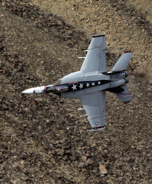 "In this Feb. 27, 2017, photo, Lt. Cmdr. Ian ""Elf"" Kibler of the VX-9 Vampire squadron from Naval Air Weapons Station, China Lake, banks his F/A-18E Super Hornet through the nicknamed Star Wars Canyon in Death Valley National Park, Calif. Military jets roaring over national parks have long drawn complaints from hikers and campers. But in California's Death Valley, the low-flying combat aircraft skillfully zipping between the craggy landscape has become a popular attraction in the 3.3 million acre park in the Mojave Desert, 260 miles east of Los Angeles. (AP Photo/Ben Margot)"