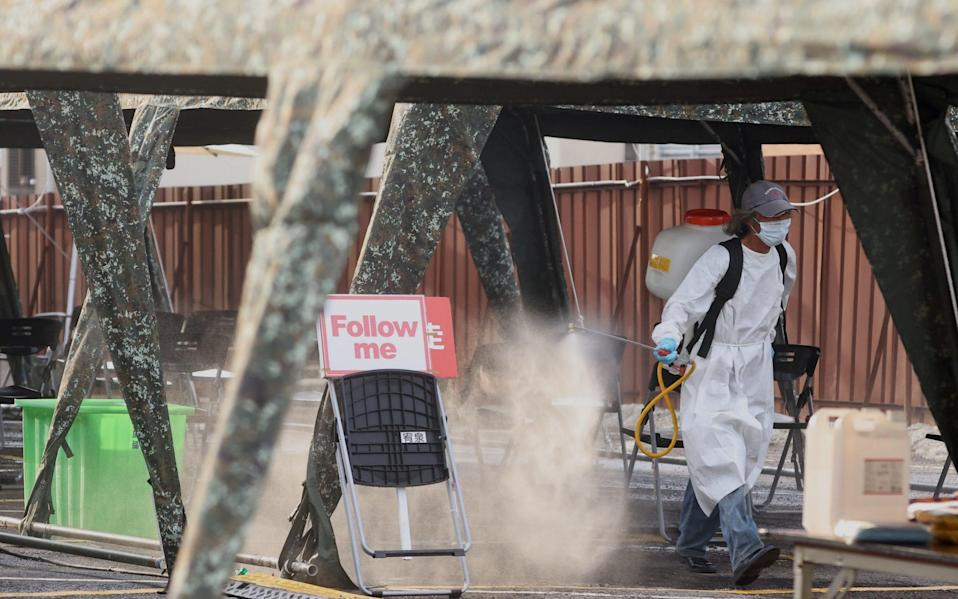 Staff disinfects a Covid-19 testing site at the Hsinchu science park, following an increasing number of locally transmitted cases in Taiwan - Reuters