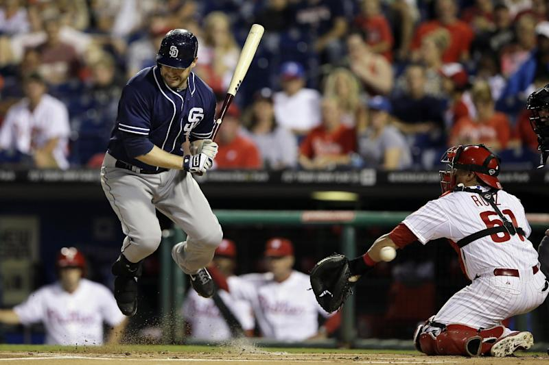 San Diego Padres' Chase Headley, left, leaps after being hit by a pitch from Philadelphia Phillies' Roy Halladay during the first inning of a baseball game, Thursday, Sept. 12, 2013, in Philadelphia. Phillies catcher Carlos Ruiz, right, is also hit by the ball. (AP Photo/Matt Slocum)