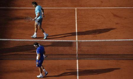 Rafael Nadal of Spain and his compatriot David Ferrer walk on the court during their men's quarter-final match at the French Open tennis tournament at the Roland Garros stadium in Paris