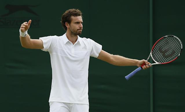 Ernests Gulbis of Latvia gestures during his first round match against Jurgen Zopp of Estonia at the All England Lawn Tennis Championships in Wimbledon, London, Monday, June 23, 2014. (AP Photo/Alastair Grant)