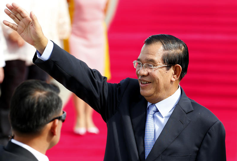 Cambodian Prime Minister Hun Sen waves to the crowd as he arrives at Clark International Airport, north of Manila, Philippines Saturday, Nov. 11, 2017. Hun Sen is one of more than a dozen leaders who will be attending the 31st ASEAN Summit and Related Summits in Manila. (AP Photo/Bullit Marquez)