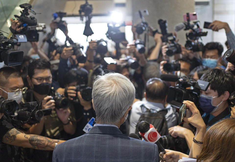 Pro-democracy activist Martin Lee, center, is surrounded by photographers outside a court after receiving a suspended sentence in Hong Kong, Friday, April 16, 2021. A Hong Kong court on Friday sentenced five leading pro-democracy advocates, including media tycoon Jimmy Lai, to up to 18 months in prison for organizing a march during the 2019 anti-government protests that triggered an overwhelming crackdown from Beijing. A total of nine advocates were given jail terms, but four of them, including 82-year-old lawyer and former lawmaker Martin Lee, had their sentences suspended after their age and accomplishments were taken into consideration. (AP Photo/Vincent Yu)