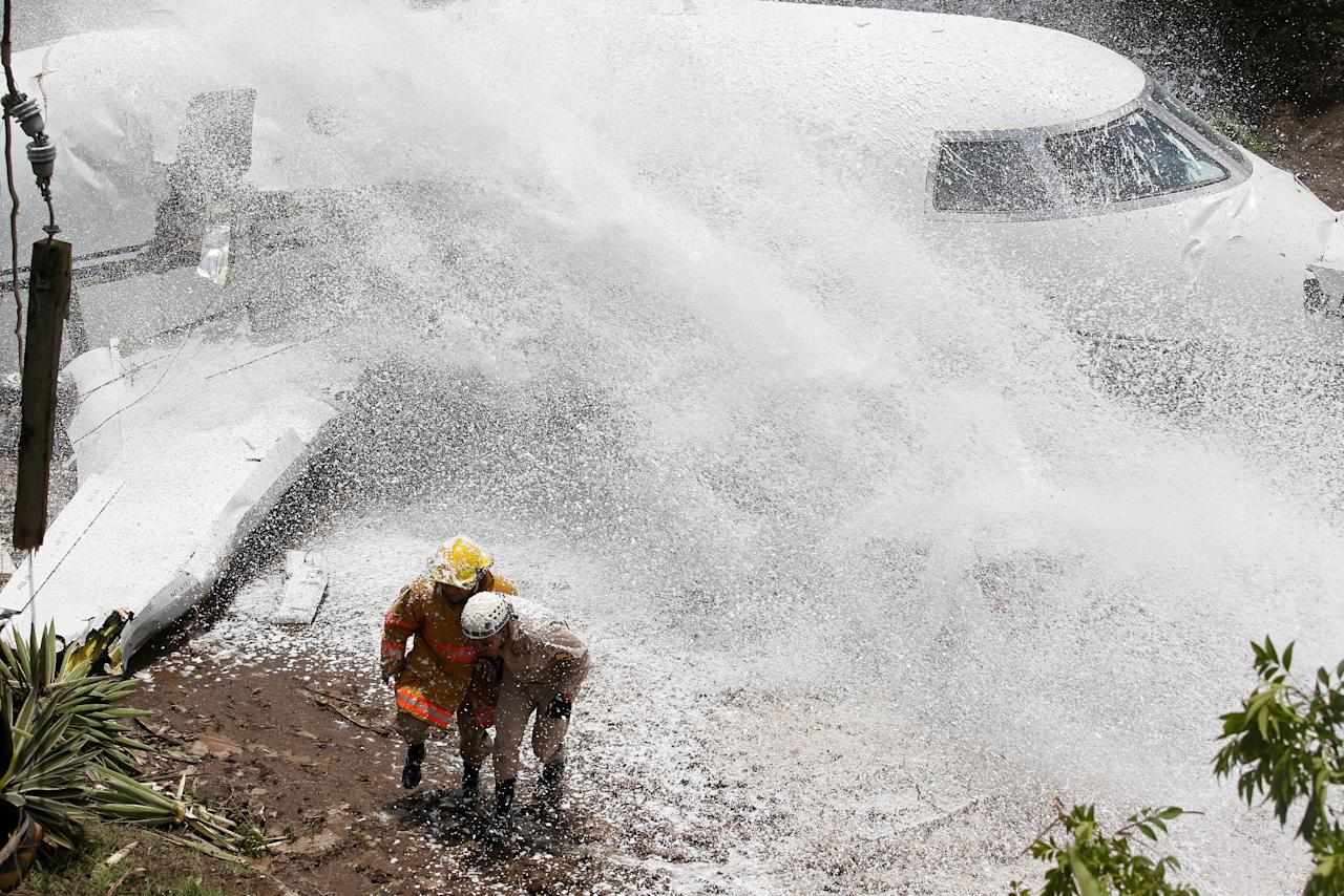 Firefighters take cover from firefighting foam applied onto the wreckage of a Gulfstream G200 aircraft that skidded off the runway during landing at Toncontin International Airport in Tegucigalpa, Honduras May 22, 2018. REUTERS/Jorge Cabrera     TPX IMAGES OF THE DAY