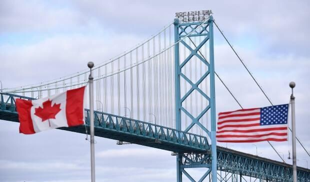 Canadian and American flags fly near the Windsor-Detroit Ambassador Bridge. (Rob Gurdebeke/The Canadian Press - image credit)