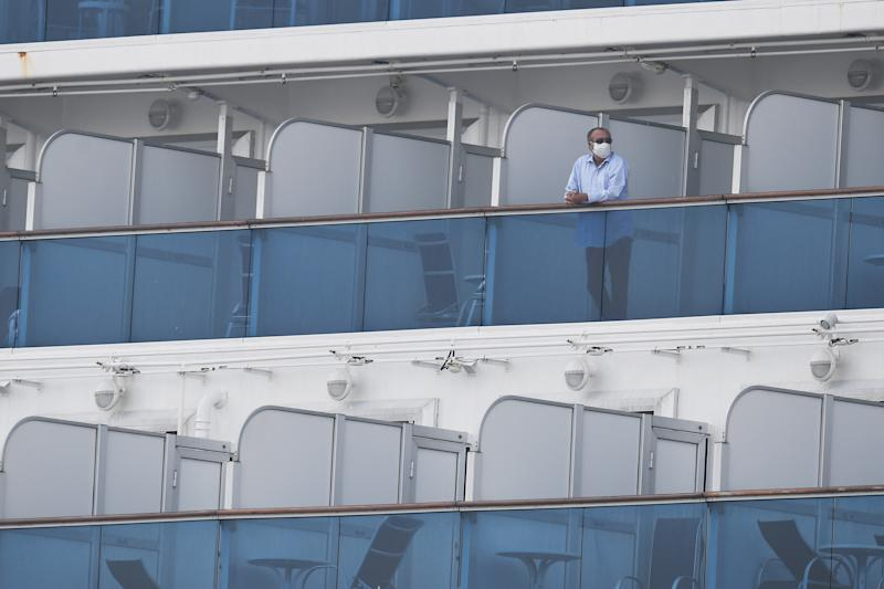 Passengers are seen on balconies of the Diamond Princess cruise ship, with around 3,600 people quarantined onboard due to fears of the new coronavirus, at the Daikoku Pier Cruise Terminal in Yokohama port.