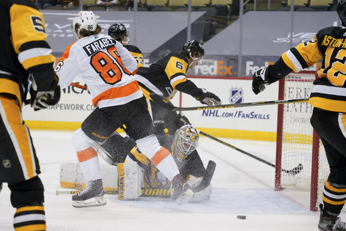 The puck bounces out after Philadelphia Flyers' Joel Farabee (86) scores on Pittsburgh Penguins' Tristan Jarry, bottom, during the second period of an NHL hockey game, Tuesday, March 2, 2021, in Pittsburgh. (AP Photo/Keith Srakocic)