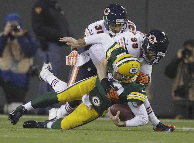Green Bay Packers quarterback Aaron Rodgers is sacked by Chicago Bears' Shea McClellin (99) and Isaiah Frey (31) during the first half of an NFL football game Monday, Nov. 4, 2013, in Green Bay, Wis. (AP Photo/Jeffrey Phelps)