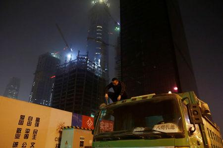 A driver repairs on the top of a truck next to construction sites at night in Beijing's central business district area, China April 16, 2017. REUTERS/Jason Lee