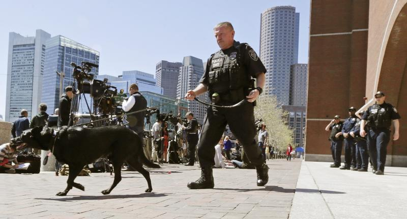 A Department of Homeland Security police officer patrols with his dog outside the Moakley Federal Courthouse in Boston, Mass., Wednesday, May 1, 2013. Three suspects were taken into custody in the Boston Marathon bombing case including two college friends of Dzhokhar Tsarneav, according to officials. (AP Photo/Charles Krupa)