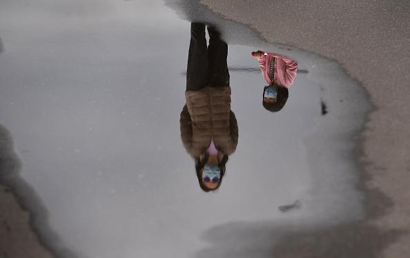 A mother and child wearing face masks are reflected in a puddle while walking in Melbourne's Docklands district.