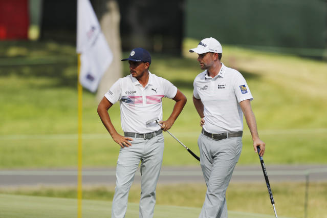 Rickie Fowler, left, talks with Webb Simpson on the 18th green during the second round of the Rocket Mortgage Classic golf tournament, Friday, July 3, 2020, at the Detroit Golf Club in Detroit. (AP Photo/Carlos Osorio)