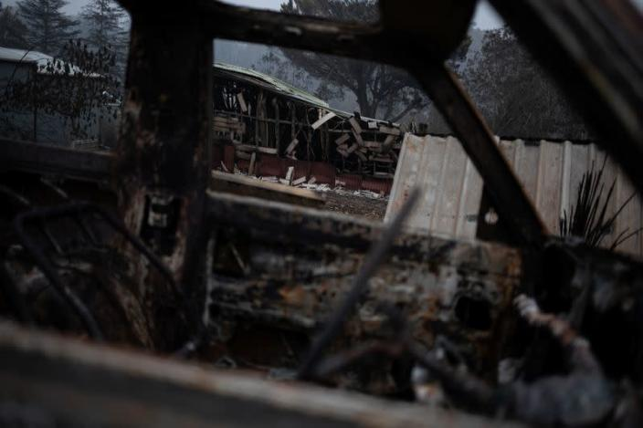 A burnt down house is seen through a destroyed car in the village of Mogo