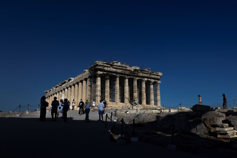 People visit the Parthenon temple atop the Acropolis hill in Athens