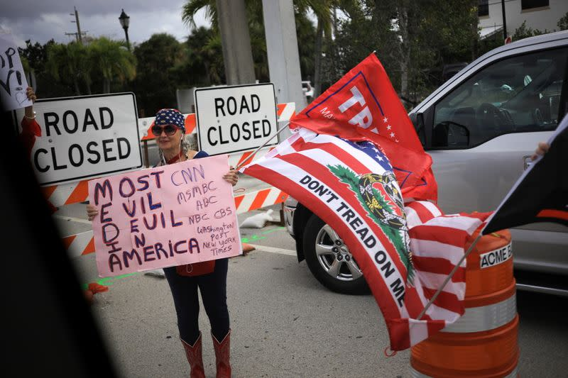 A supporter of President Trump displays a sign as the presidential motorcade passes through West Palm Beach