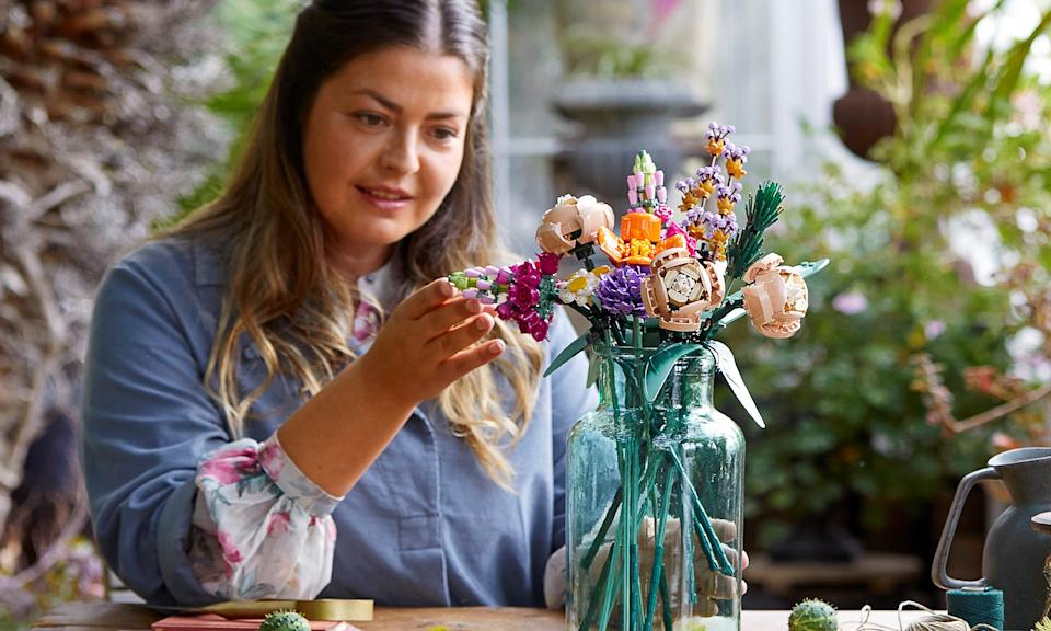 A women inspects a bouquet of LEGO flowers in glass vase.