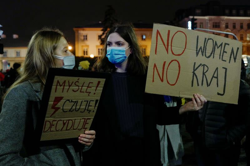 Demonstrators hold placards during an anti-government protest in Warsaw