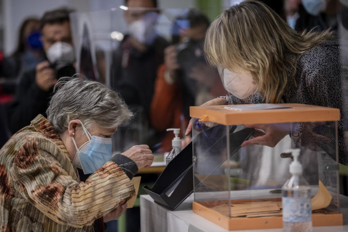 An elderly woman places her identification card on a tray before casting her vote during the regional election in Madrid, Spain, Tuesday, May 4, 2021. Over 5 million Madrid residents are voting for a new regional assembly in an election that tests the depths of resistance to lockdown measures and the divide between left and right-wing parties. (AP Photo/Bernat Armangue)