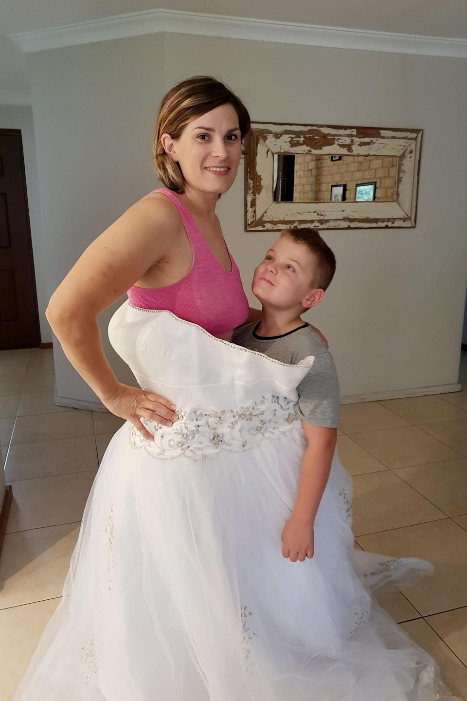 Belinda Brodie pictured with her son wearing the wedding dress [Photo: Caters]
