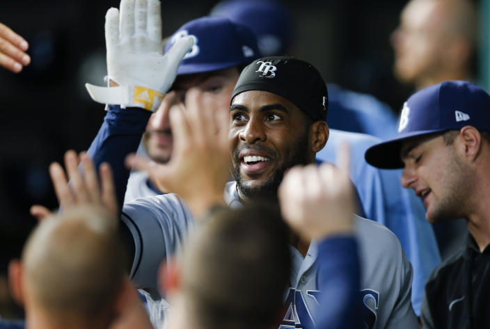 Tampa Bay Rays' Yandy Diaz (2) is congratulated by teammates after scoring on a two-RBI single hit by Austin Meadows during the first inning of a baseball game against the Texas Rangers, Saturday, June 5, 2021, in Arlington, Texas. (AP Photo/Brandon Wade)