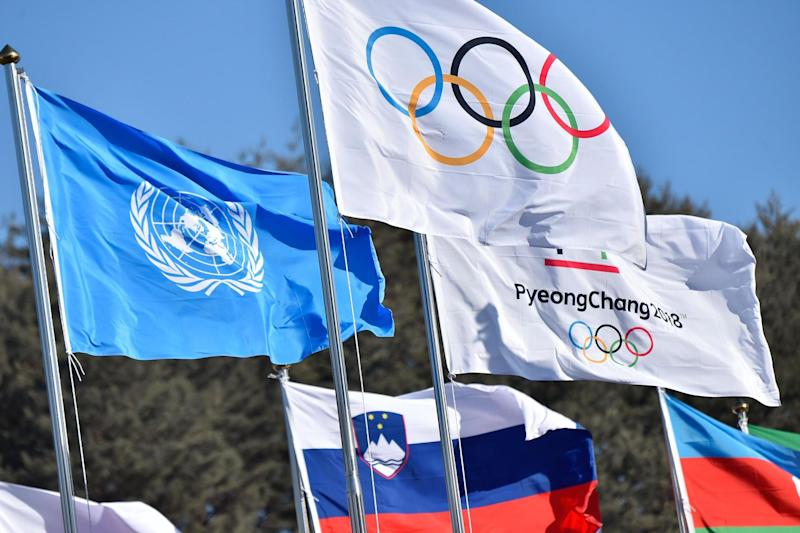The Olympic flag flies next to the United Nations flag at the Olympic village, in PyeongChang: Loic Venance/AFP/Getty Images